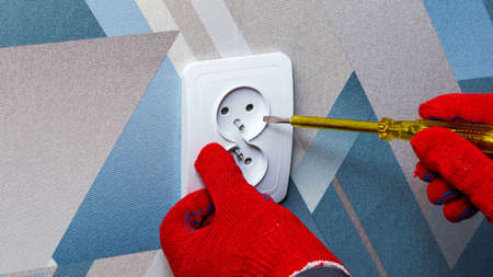 An electrician wearing red protective gloves uses a screwdriver to install a socket into the wall of the living room. Close-up of hands. Home master concept.
