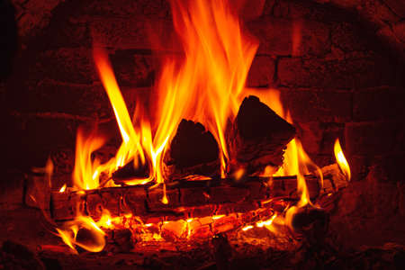 Background with burning firewood in a brick fireplace. Warmth and comfort