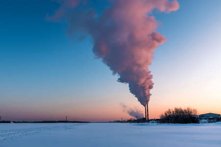 Winter cityscape at dawn with smoking factory chimneys on the banks of a frozen river. Environmental pollution