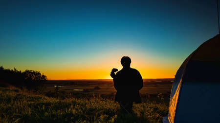 Silhouette of a man with binoculars near the tent against the backdrop of the sunset on a clear sky over the meadow. Tourism and travel concept.