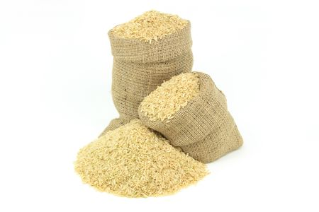 sackcloth: Brown rice over white. Still picture displaying brown rice  spilled on pile and in burlap sacks over white background.