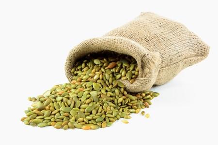 sementi: Ancora foto di sacchi di tela ruvida completi con semi di zucca e semi versati su sfondo bianco.