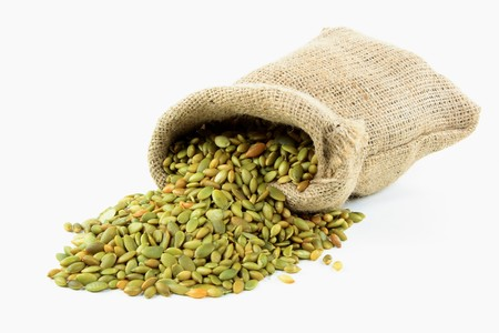 Still picture of burlap bags full with Pumpkin seeds and spilled seeds over white background.  Stock Photo