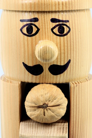 Picture of wooden (not painted plain wood) nutcracker upper part shaped and drown as man ready to crack a walnut.  photo