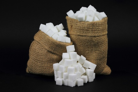 Picture of Sugar Cubes in Burlap Bags and spilled on pile  over black Background.  Stock Photo