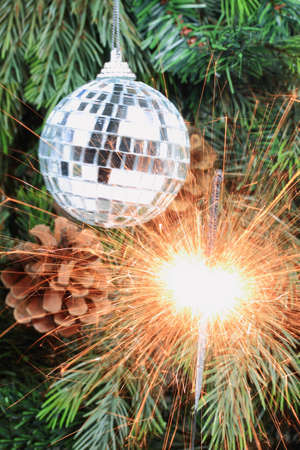 focal point: Picture of burning (lit) sparkler - focal point, and green Christmas tree, pine cones and decorative mirror ball as blurred background - Vertical orientation.