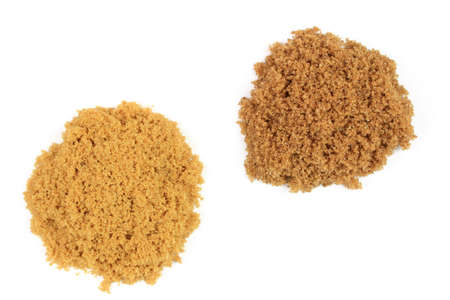 Two type brown sugar spilled on pails over white background, light brown pile is natural classic Brown Sugar and darker brown pile is Brown sugar with special flavour and crunchy texture.