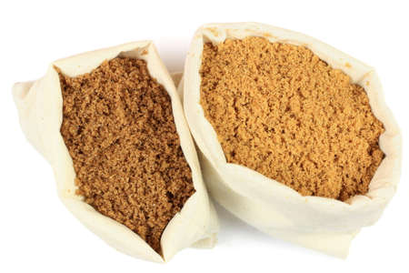 Two bags from white fabric full with different types brown sugar over white background, light brown natural classic Brown Sugar and darker Brown crunchy texture Brown Sugar with special flavour.    Zdjęcie Seryjne
