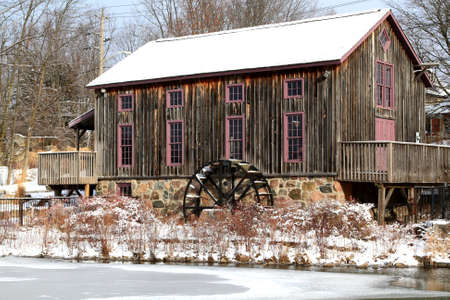 Picture of old (historical building) grist (flour) mill in Waterloo Ontario on almost frozen Beaver Creek in snow cold winter day.