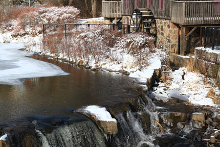 Picture of detail Waterwheel old grist (flour) mill in Waterloo Ontario on almost frozen Beaver Creek in snow cold winter day.