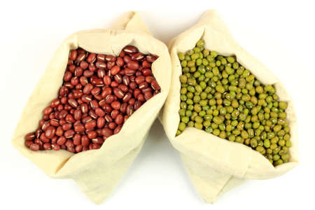 azuki bean: From Top close view of Organic seeds of Azuki bean (red seeds) and Mung bean (green seeds) in white fabric bags over white background.