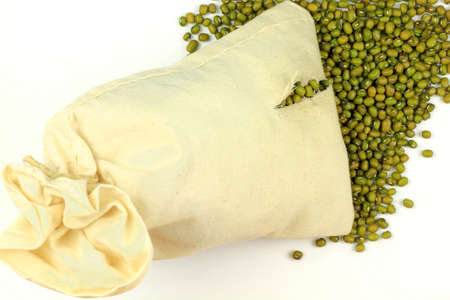 Picture of spilled from broken white fabric bag seeds of Organic Mung Bean over white background. Stock Photo - 11915052