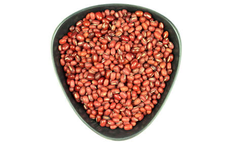 azuki bean: From Top close view of Organic Azuki bean seeds (Red Bean), (red seeds) in black pottery bowl over white background.