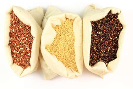 Seeds of Red, fehér és fekete Organic quinoa zsákokban fehér anyagból mint a fehér háttér. Quinoa gabona-szerű termesztett elsősorban annak ehető magvak.