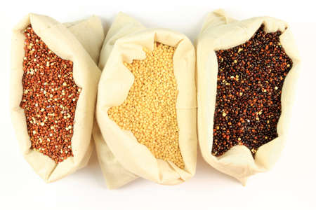 Seeds of Red, White and Black Organic Quinoa in sacks from white fabric over white background. Quinoa is a grain-like crop grown primarily for its edible seeds.