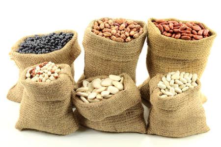 Foto van verschillende soorten Bean Seeds (peulvruchten, puls) in jute zakken (zakken) vooraanzicht op een witte achtergrond.