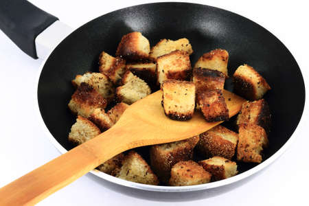 Frying in Pan Bread  cubes  pieces in butter to prepare Croutons over white background