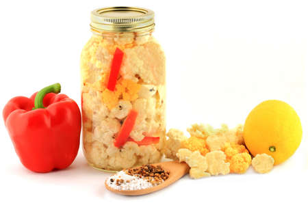 pickling: Florets Orange and White Cauliflower for pickling with lemon, pieces sliced Red Pepper in a glass jar, Pickling Salt and Seasoning in wooden cooking spoon, over white background