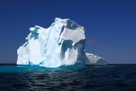 Iceberg after traveling 1600 km from Western Greenland to Iceberg Alley around East coasts of Labrador and Newfoundland already loss big part of its ice mass by melting and breaking on small pieces 스톡 콘텐츠