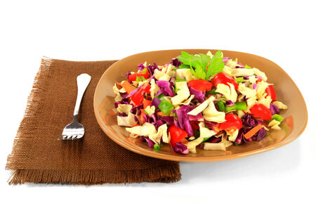 Salad from mixed chopped red and white cabbage  coleslaw  seasoned with chopped bell peppers  red and green , leaves of celery, grated carrots, served on plate over brown fabric napkin over white
