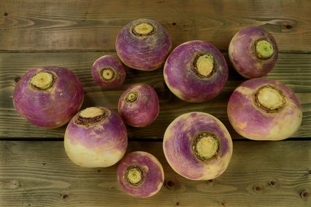 白紫、低カロリー、高ビタミン C 野菜非常に菜食主義の食糧として肉の食事への側面の調理で使用される木製の灰色テーブル上のカブの根のピュー