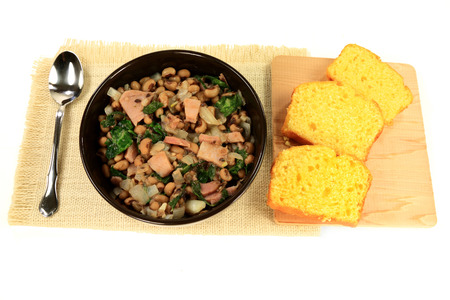 Served in black bowl New Years Day Traditional American South cooked meal Chopped Ham and Collard Greens Blackeyed Pea Onion white serviette Slices Corn Bread Spoon over white background