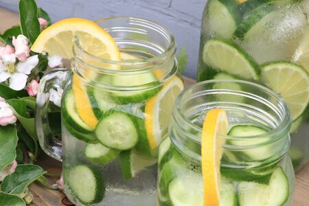 In hot summer day on the table decorated with apple tree blooms in backyard is served Naturally Flavored Infused Cucumber water with ice and lemon and lime slides