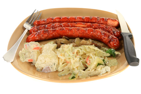 Grilled Smoked Sausages served on brown Porcelain plate dish garnished with potato salad, Coleslaw, Onion salad with feta cheese and marinated mushrooms over white background isolated