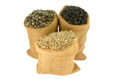 Different kind (sorts) (Black Oil known as well as bird seeds, Striped and Hulled known as well unshelled) Sunflower seeds in burlap bags (sacks) over white background