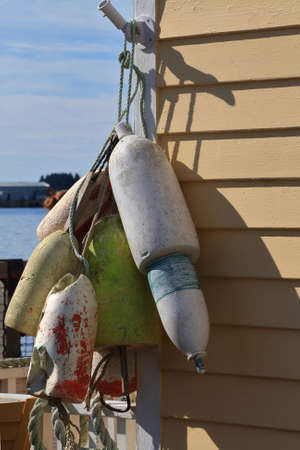 Different sizes, shapes and made from wood,  plastic Floats for Fishnet (fishing net) hang up outside on sun to dry from oceanic water Stock Photo