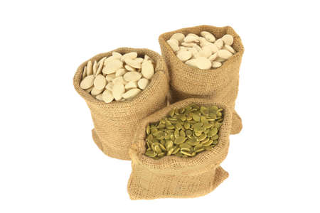 With shell and Hulled (unshelled) Pumpkin seeds in burlap bags (sacks) over white background Stock Photo