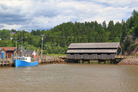 Built in 1935 still in use Covered Wooden Bridge Irish River #1 or Vaughan Creek Bridge St. Martins area New Brunswick, part of marina for commercial lobster fishing in moment of high tide Stock Photo