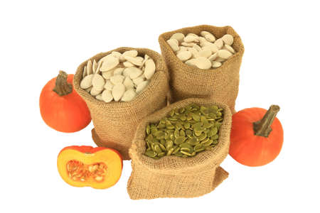 With shell and Hulled (unshelled) Pumpkin seeds in burlap bags (sacks), spherical  pumpkins and half pumpkin with visible seeds over white background Stock Photo