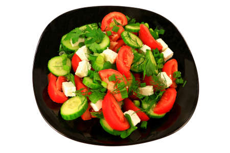 Mediterranean style salad from tomato wedges, sliced seedless cucumber, Feta cheese seasoned with green onion, parsley, and dill served on a black porcelain dish over white background