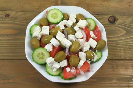 Greek salad from fresh organic vegetables: chopped red onion, tomatoes cut on wedges, sliced seedless cucumber; and stuffed green colossal olives, cubes goat Feta Cheese in white dish on wooden table Stock Photo