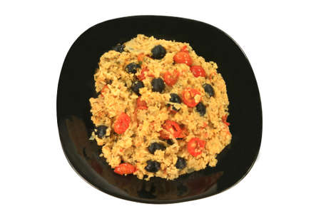 Healthy Vegetarian Mediterranean Style meal of rice, onion, small cherry tomatoes (cut in half and whole), black olives, seasoned with parsley flakes and red pepper, served on a black porcelain dish Stock Photo