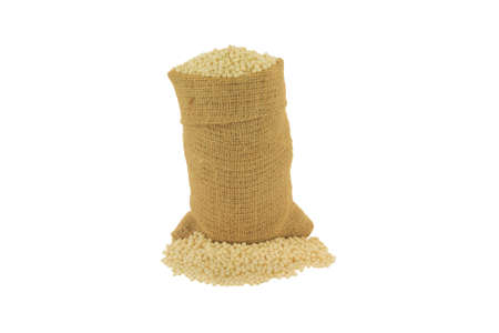 Raw (uncooked) Israeli Couscous in burlap bag and spilled out on pile over white background - isolated Stock Photo