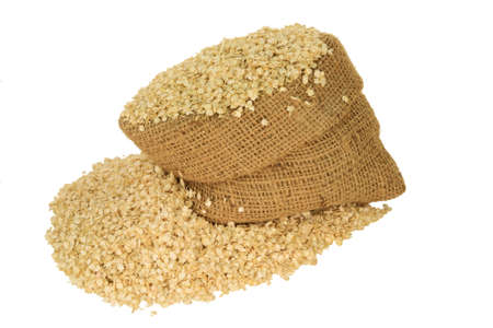 Processed to Flakes Organic Quinoa seeds in burlap bag and spilled out on pile isolated over white background Stock Photo