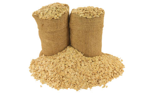 In Burlap Bags, spilled out on pile LARGE FLAKE OATS, ROLLED OATS FLATTENED BETWEEN ROLLERS to produce oatmeal on Large Flakes thick enough to hold shape during cooking isolated on white background Stock Photo