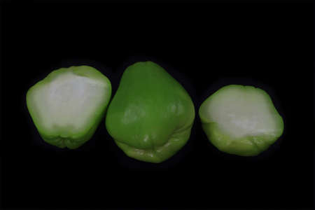 Containing mostly water green colored Pear shaped Fresh organic Chayote Squash (fruit) outside (green skin) inside (white to light yellow flash) Reach on water vitamin C and B over black background