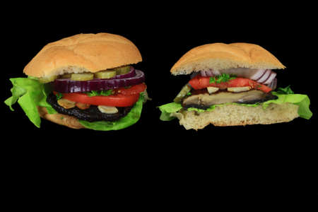 Vegan Burgers from grilled cap Organic Portobello mushroom, Lettuce, slices tomato, red onion, pickle, fried garlic, parsley in whole wheat hamburger bun, entire and cut on half on black background Stock Photo
