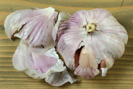 Bulb of Organic Dry Garlic and Peels over wooden table Stock Photo