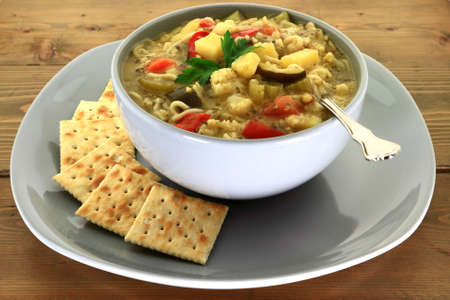 Gardener style gourmet vegetables vegetarian soup with added noodles  served with salty soda crackers side in grey porcelain bowl over plate on wooden garden table decorated with struck plain parsley Stock Photo