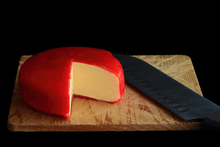Wheel of Gouda Cheese covered with red wax protective layer over wooden cutting board, knife with which is cut a segment (wedge) of the cheese in order cheese to be seen over black background