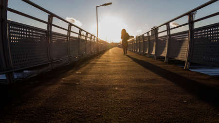 pedestrian bridge: woman silhouette  in sunset on pedestrian bridge