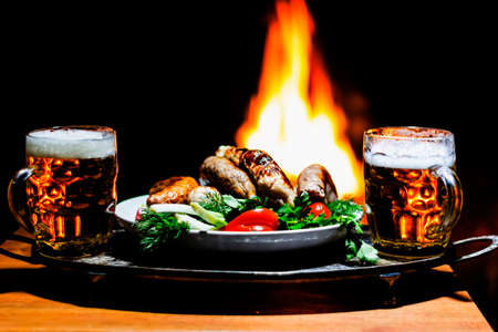 beers: two beers and sausages with fireplace on background