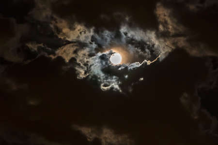 the moon coming through the clouds