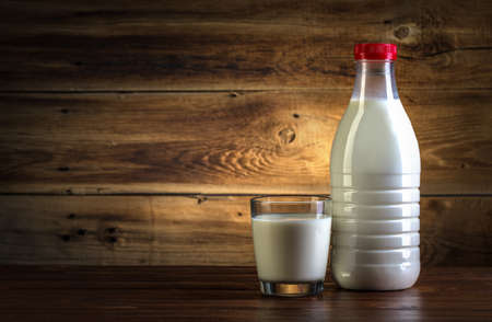 glass and bottle of milk on wooden background Stock Photo