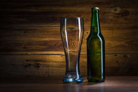 Beer bottle and empty glass of beer photo