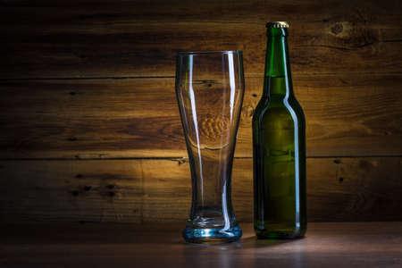 Beer bottle and empty glass of beer